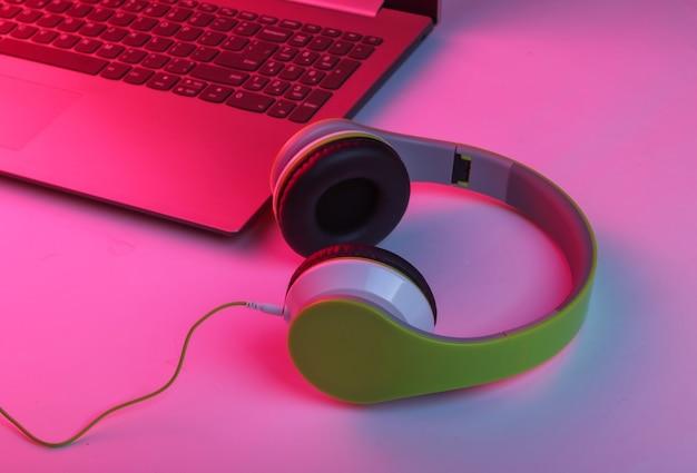 Portátil y auriculares con luz neón azul-rosa
