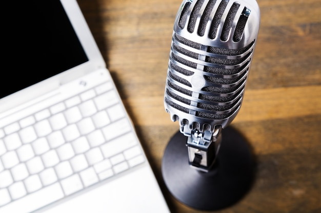 Portátil blanco abierto con micrófono sobre fondo de mesa de madera