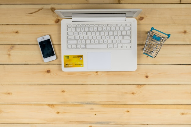 El portátil blanco con teléfono inteligente, tarjeta de crédito y el modelo de carro de compras en el fondo de la mesa de madera. compras de comercio electrónico.