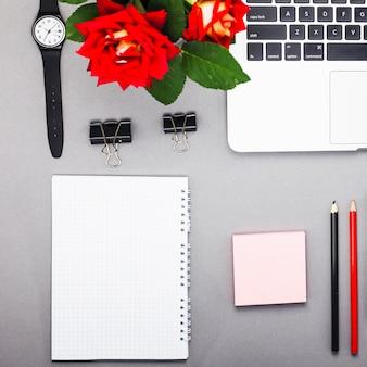 Portátil con bloc de notas en blanco en la mesa