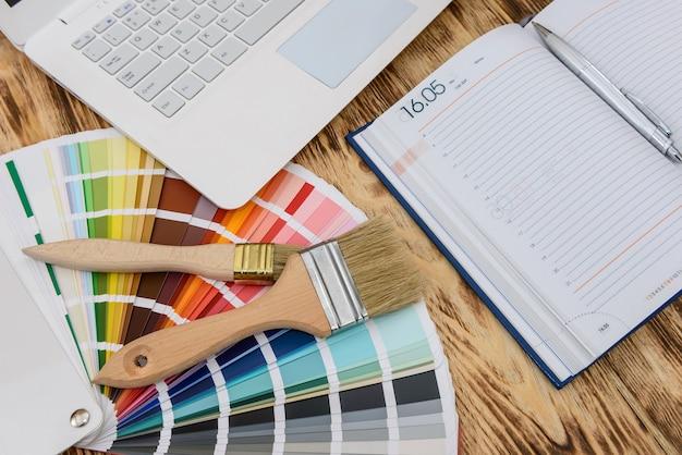 Portátil con bloc de notas y muestra de color en la mesa