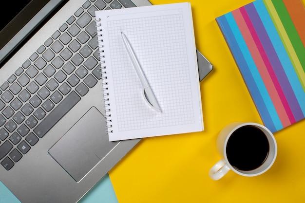Portátil y bloc de notas con taza de café