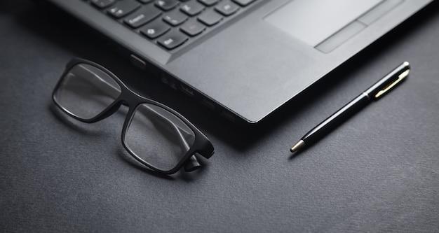 Portátil, bolígrafo y gafas en el negro.