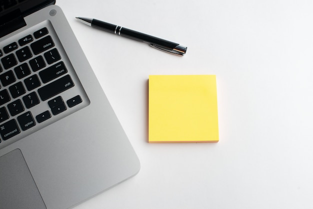 Portátil con bolígrafo negro y nota amarilla.