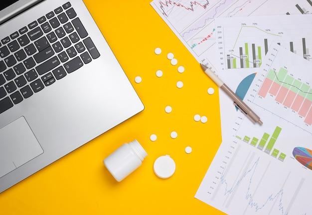 Portátil con botella de píldoras, gráficos y tablas sobre un fondo amarillo. plan de negocios, analítica financiera, estadísticas médicas.