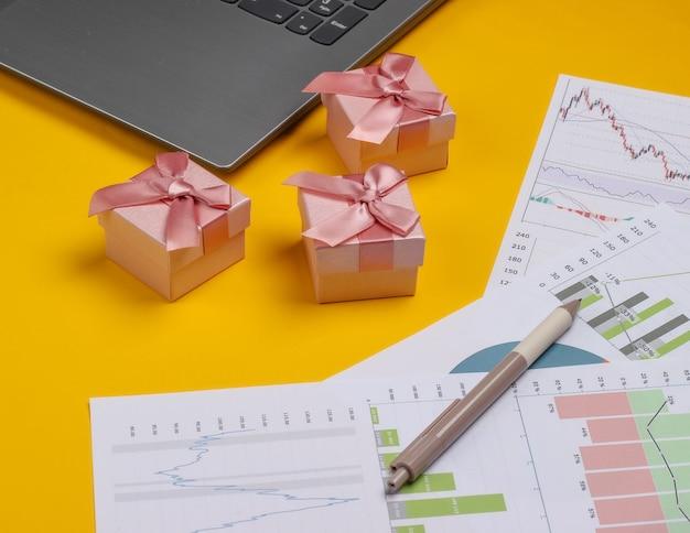 Portátil con cajas de regalo, gráficos y tablas sobre fondo amarillo. plan de negocios, analítica financiera, estadísticas.