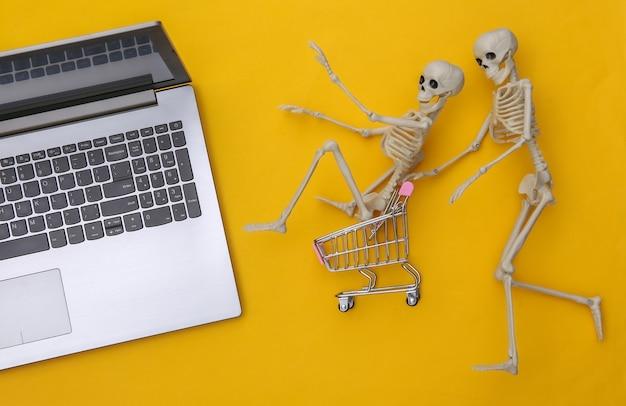 Portátil y carrito de la compra con esqueletos sobre un fondo amarillo. supermercado online. tema de halloween. vista superior