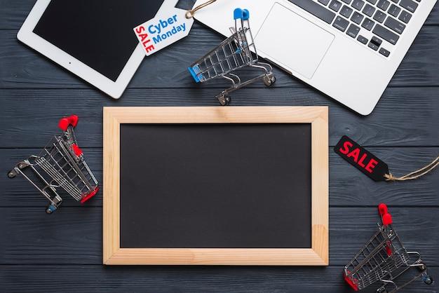 Portátil cerca de etiqueta, tableta, carrito de supermercado y marco de fotos