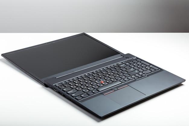 Portátil convertible abierto. plantilla de pantalla de portátil para diseño digital de sitio web portátil abierto vacío con maqueta en la mesa de escritorio blanco con pantalla en negro. espacio de trabajo minimalista con un moderno portátil convertible.