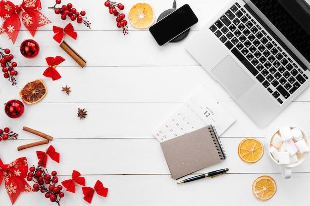 Portátil en el escritorio de madera blanca rodeada de adornos navideños rojos