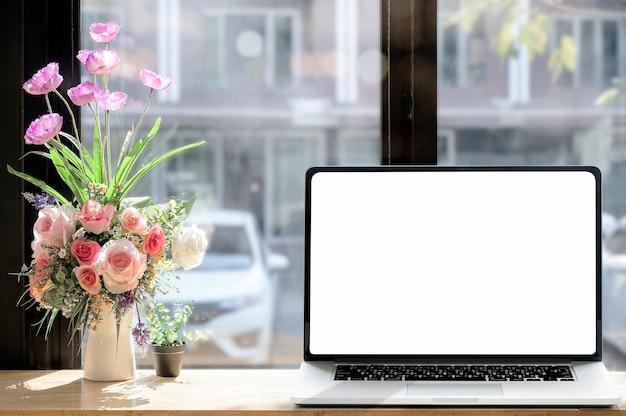 Portátil con espacio en blanco en la mesa de madera en la cafetería. pantalla en blanco para diseño gráfico.