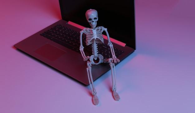 Portátil y esqueleto en luz degradada de neón azul rojo.