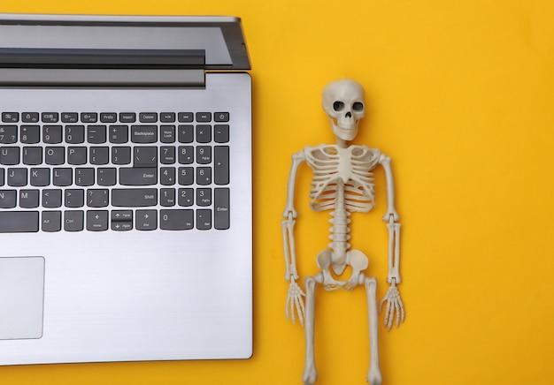Portátil y esqueleto sobre un fondo amarillo. vista superior