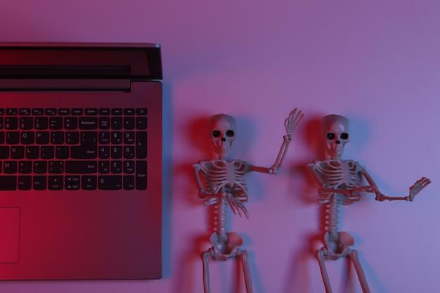 Portátil y esqueletos en luz degradada de neón azul rojo. vista superior