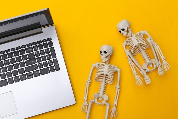 Portátil y esqueletos sobre un fondo amarillo. vista superior