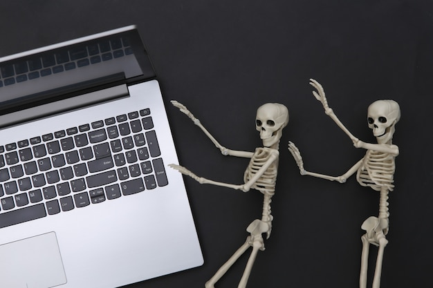 Portátil y esqueletos sobre fondo negro. tema de halloween. vista superior
