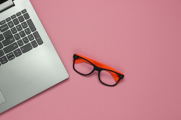 Portátil y gafas sin lentes sobre un fondo rosa pastel. concepto de autónomo. endecha plana. vista superior