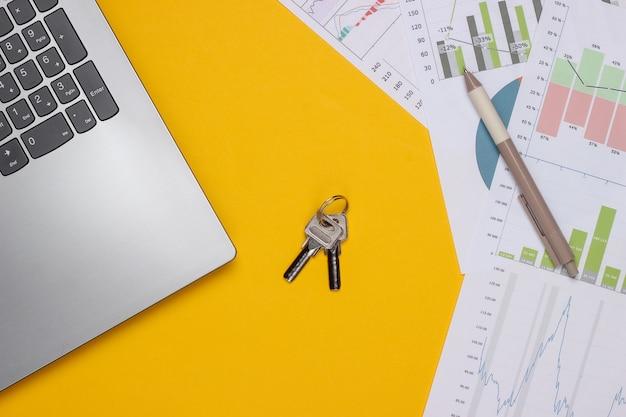 Portátil con gráficos y tablas, clave sobre un fondo amarillo. plan de negocios, analítica financiera, estadísticas. vista superior
