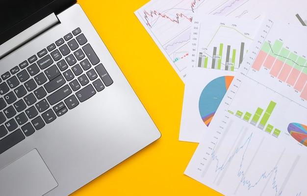 Portátil con gráficos y tablas sobre un fondo amarillo. plan de negocios, analítica financiera, estadísticas. vista superior