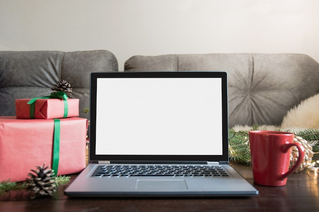 Portátil en el interior de la casa para reservar, busque una oferta especial de navidad espacio para texto en pantalla. planeando vacaciones.