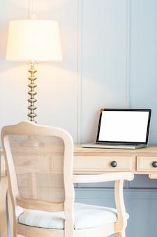 Portátil y lámpara de luz sobre mesa.