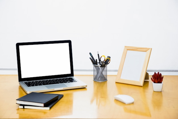 Portátil con marco en blanco en mesa de madera