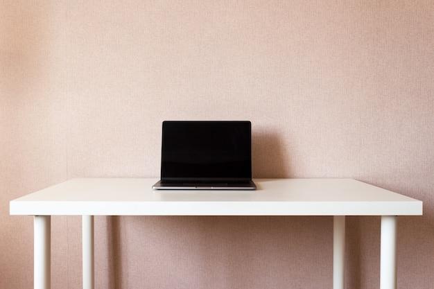 Portátil en mesa blanca, espacio de trabajo