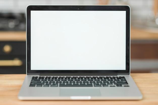 Portátil moderno con pantalla blanca en blanco en mesa de madera