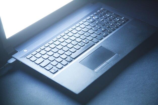 Portátil negro en el escritorio de oficina negro. concepto de tecnología
