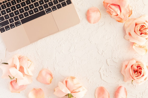 Portátil de oro rosa en el escritorio de la mesa de oficina con flores rosas y pétalos aislados en blanco con textura concreta