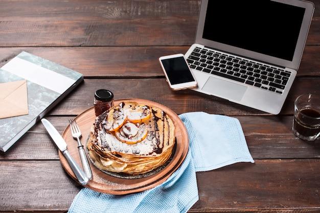 Portátil y panqueques con jugo. desayuno saludable
