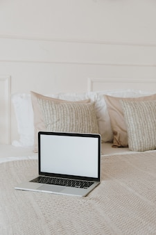 Portátil de pantalla en blanco en la cama con almohadas y ropa de cama. dormitorio de estilo clásico, diseño de interiores de casa.