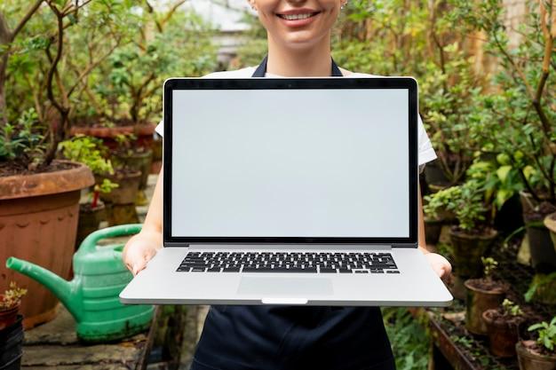 Portátil de pantalla en blanco en un invernadero