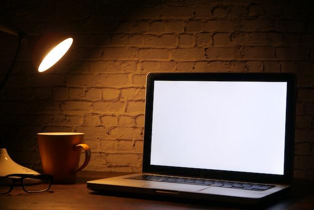 Portátil con pantalla en blanco con lámpara de mesa en el escritorio.