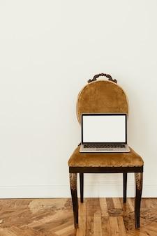 Portátil de pantalla en blanco en silla clásica. diseño de interiores de viviendas. copie la plantilla de espacio.