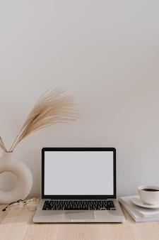 Portátil con pantalla de espacio de copia en blanco en la mesa con ramo de hierba de la pampa en florero, vasos, revistas y taza de café