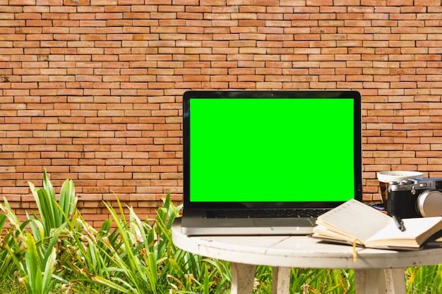 Portátil con pantalla negra en blanco con cámara, taza de café portátil en mesa de madera con pared