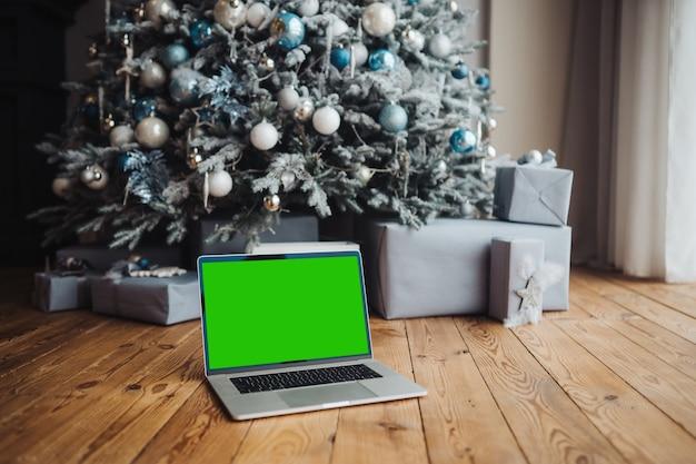Portátil con pantalla verde cerca de las decoraciones de año nuevo
