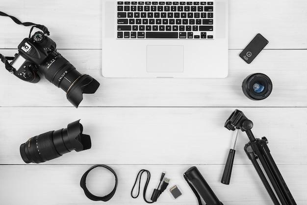 Portátil rodeado de accesorios de cámara en escritorio de madera blanca