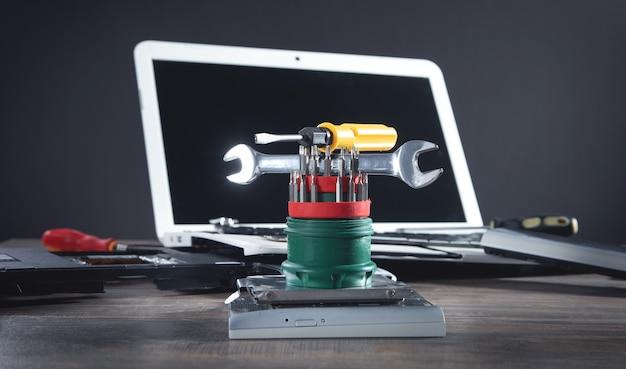 Portátil roto con una llave y un destornillador sobre la mesa. servicio de reparación de computadoras