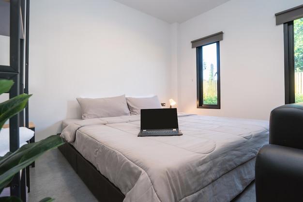 Portátil sobre una cama en un dormitorio moderno