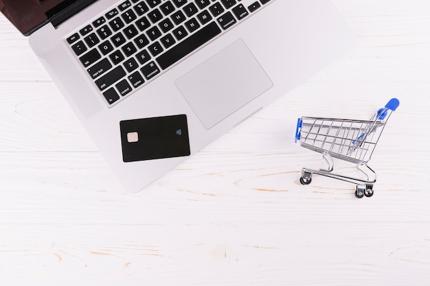 Portátil de tarjeta de viaje con carrito de compras en miniatura en el escritorio de madera
