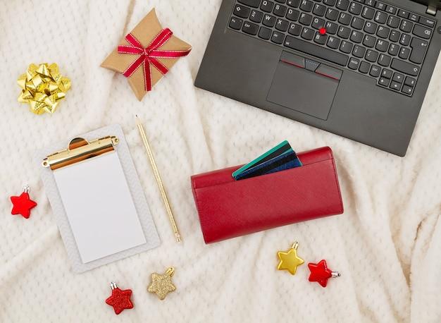 Portátil, tarjetas de crédito, monedero y decoración navideña. compras navideñas en línea, compra de regalos