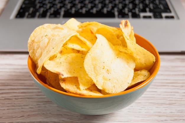 Portátil y tazón de papas fritas en la mesa de madera. concepto de malos hábitos