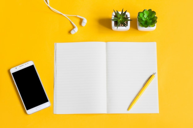 Portátil, teléfono móvil, plantas, bolígrafo, auriculares en amarillo