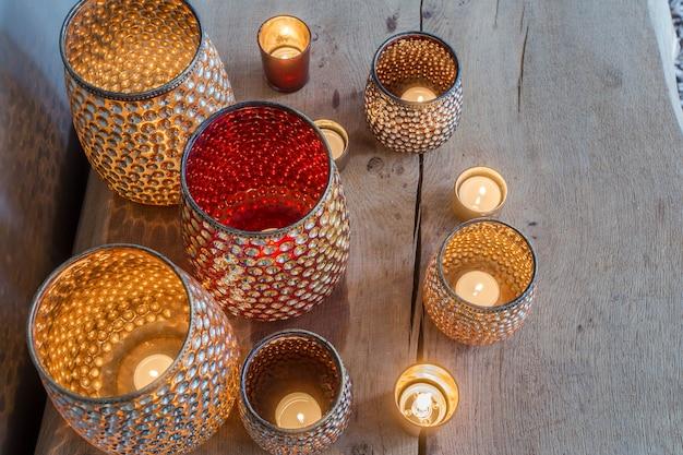 Portavelas de color naranja colorido en la mesa de madera con destellos de diseño árabe
