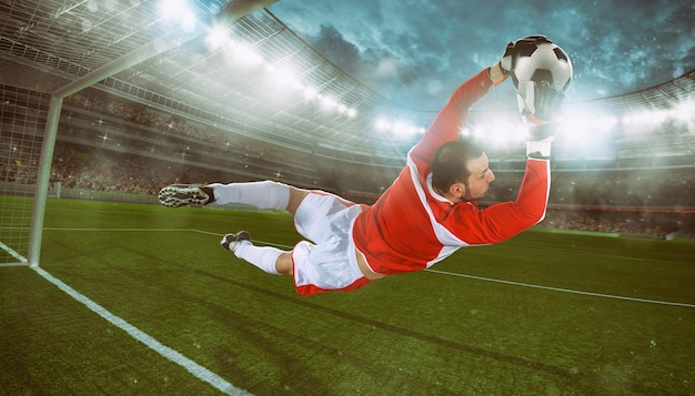 El portero atrapa el balón en el estadio durante un partido de fútbol.
