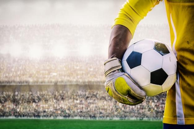 Portero con un balón de fútbol en el estadio