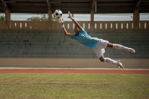 Portero de fútbol en acción en el estadio de fútbol