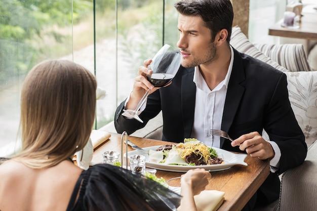Portirat de una hermosa pareja bebiendo vino en restaurante.
